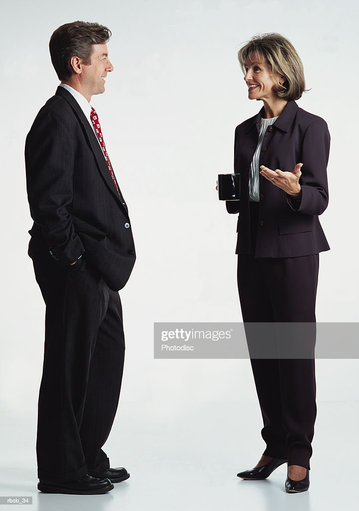 a handsome middle aged caucasian business man and an attractive middle aged business woman in dark business suits are conversing with eachother : Foto de stock