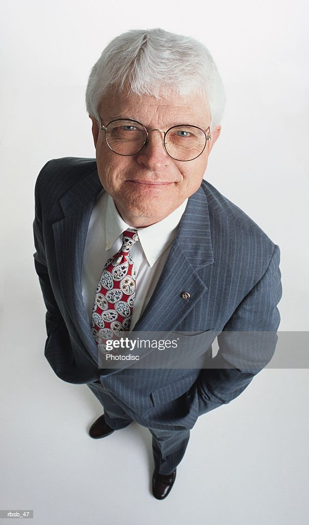 a handsome middle aged caucasian businessman with glasses and white hair is dressed in a grey suit with his hand in his pockets and looking up at the camera : Foto de stock