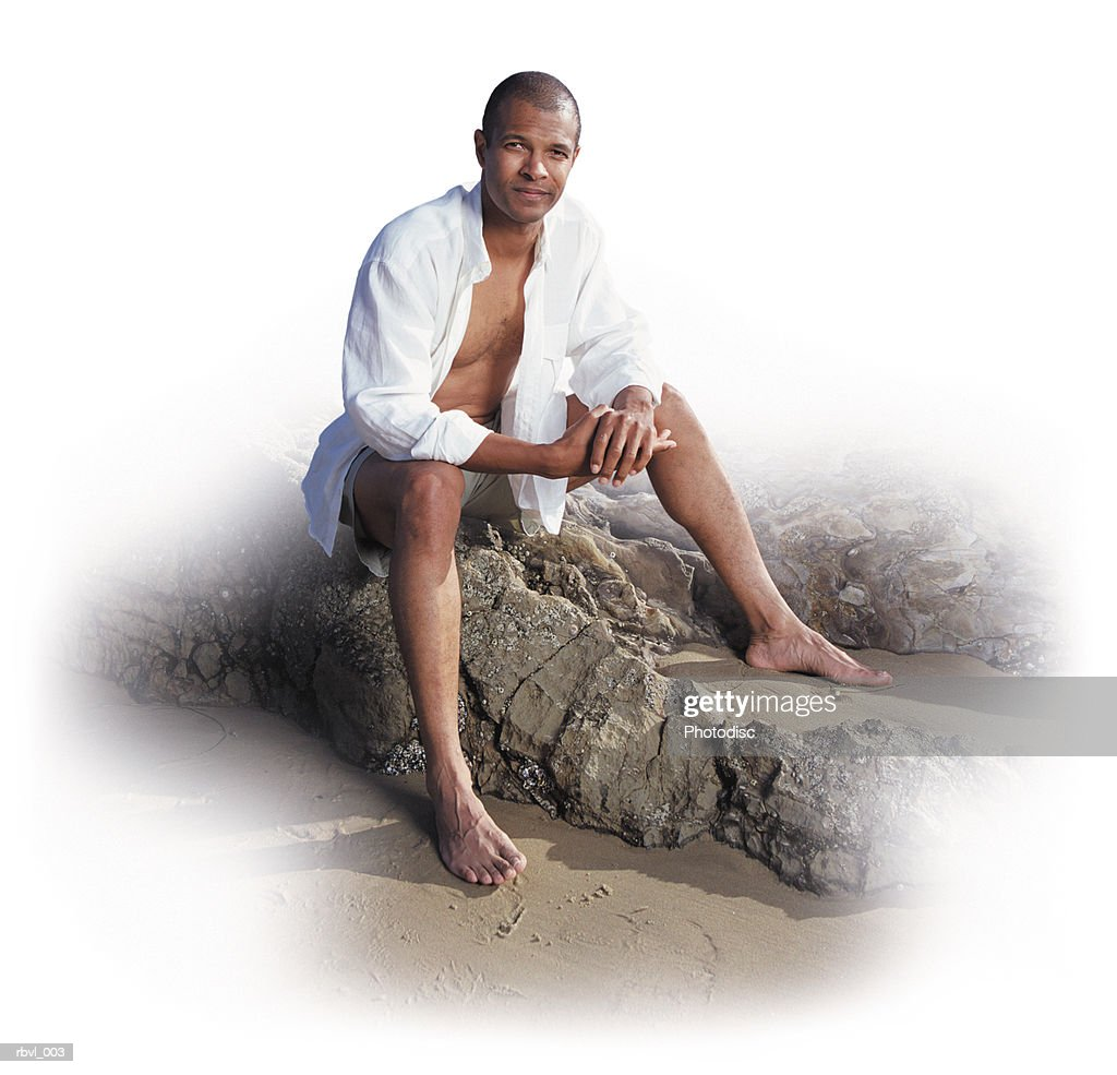 a handsome young adult african american man in an unbuttoned white shirt and tan shorts is sitting on a rock along the beach : Stock-Foto