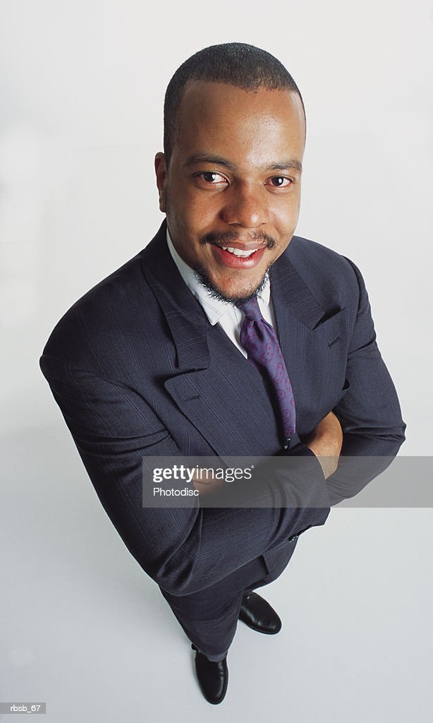 a handsome young african american man in a dark business suit and purple tie looking up into the camera with his arms crossed : Foto de stock