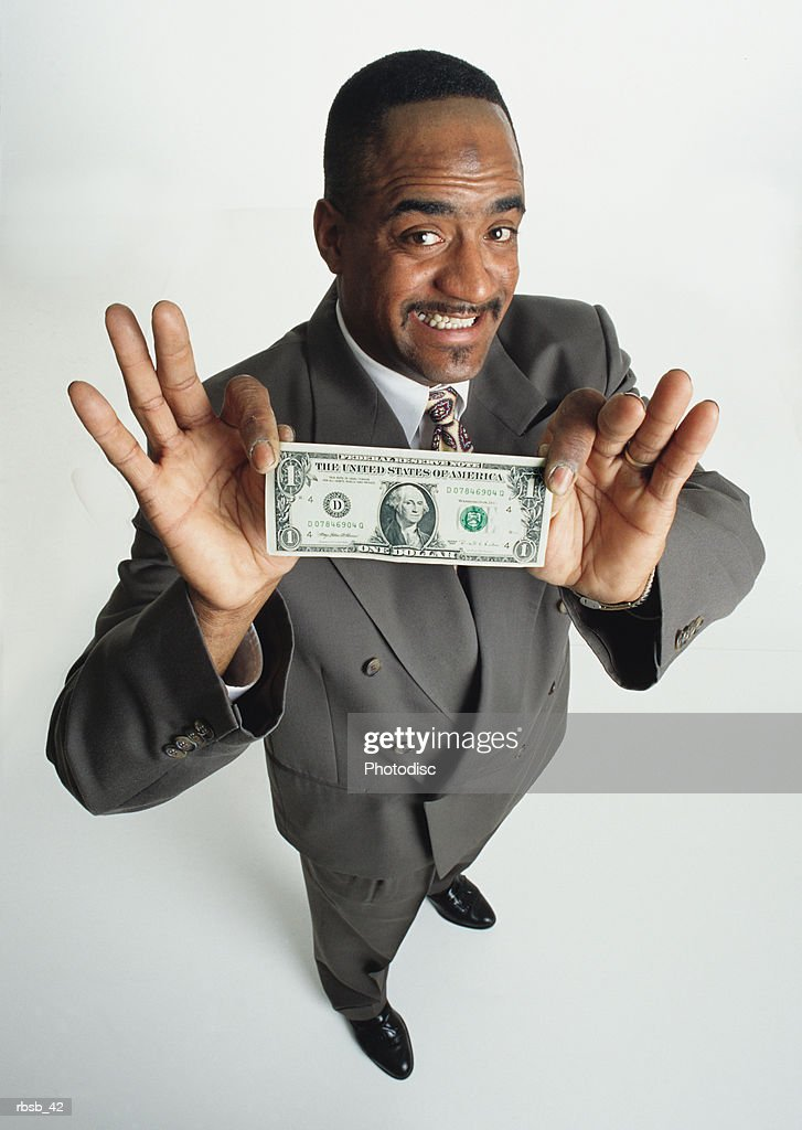 a handsome young african american man in grey business suit is presenting a dollar bill to the camera : Bildbanksbilder