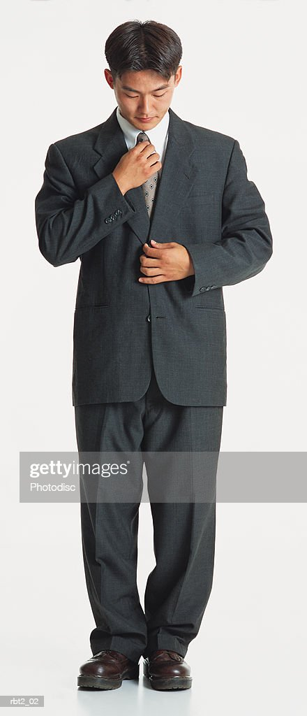 a handsome young asian man wearing a dark suit adjusts his tie while looking down : Foto de stock
