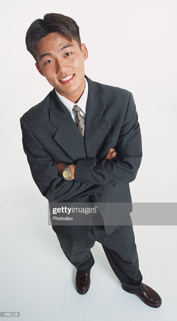 a handsome young asian man wearing a dark suit and standing with arms crossed looks up at the camera : Stockfoto