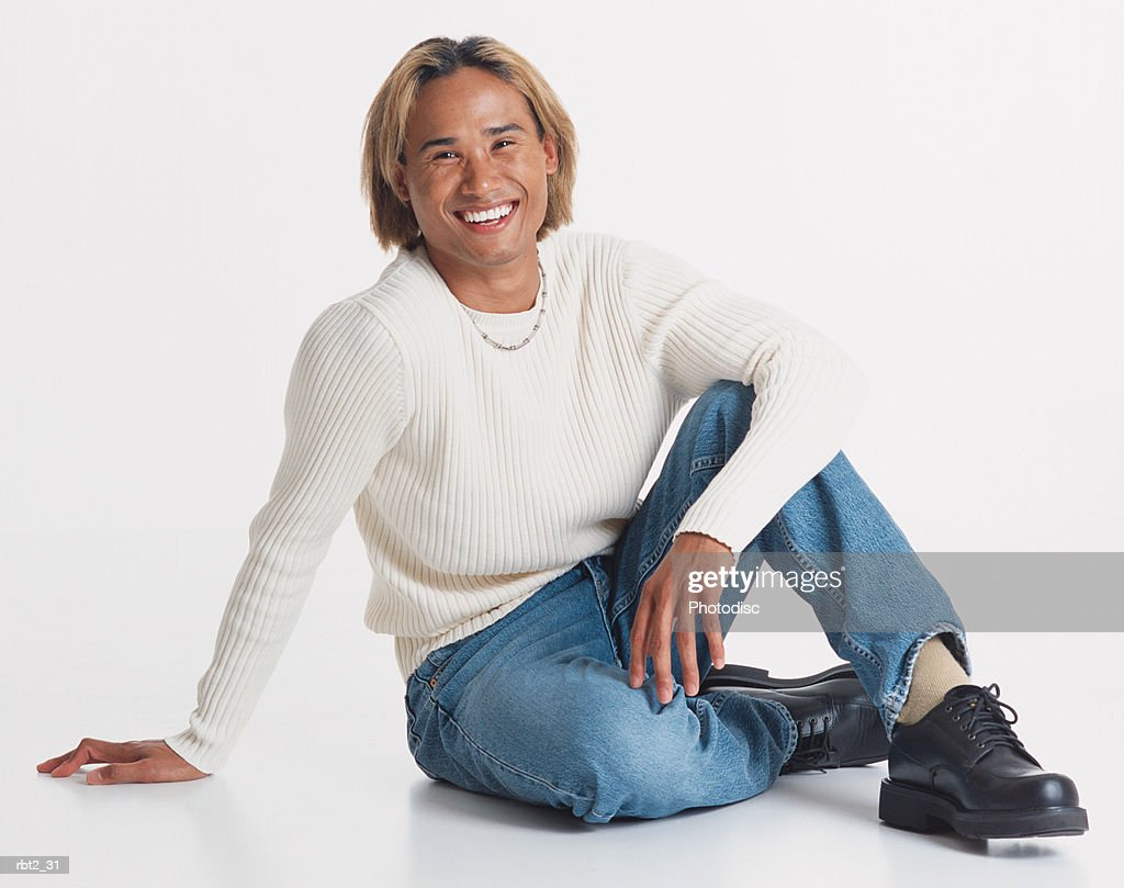 a handsome young asian man with bleached hair wearing jeans and a long sleeve white teeshirt sits casually on the floor : Foto de stock