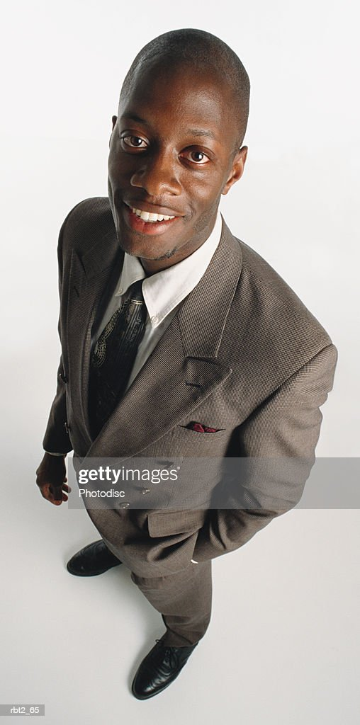 a handsome young  bald african american man wearing a gray double breasted suit and tie is standing with one hand in his pocket looking up at the camera : Foto de stock