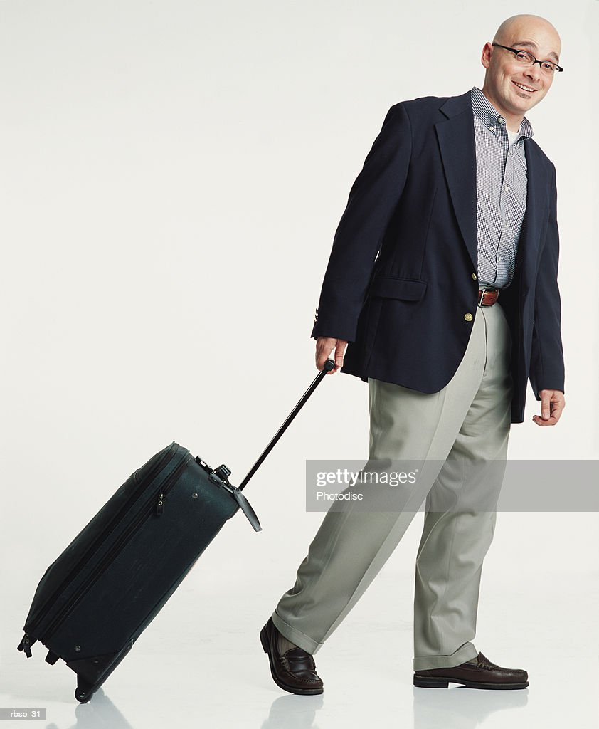 a handsome young bald caucasian man with glasses is dressed in a blue blazer and tan pants walks and pulls a suitcase behind him while smiling at the camera : Foto de stock