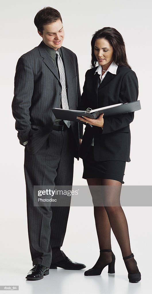 a handsome young caucasian business man in a dark grey suit and a beautiful young ethinic businesswoman with long dark hair dressed in a black suit conversing with eachother looking at a portfolio : Stockfoto