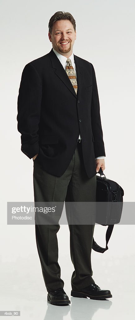 a handsome young caucasian businessman with a beard and dark hair dressed in a dark blazer and dark grey pants looking into the camera with a briefcase in his hand : Foto de stock