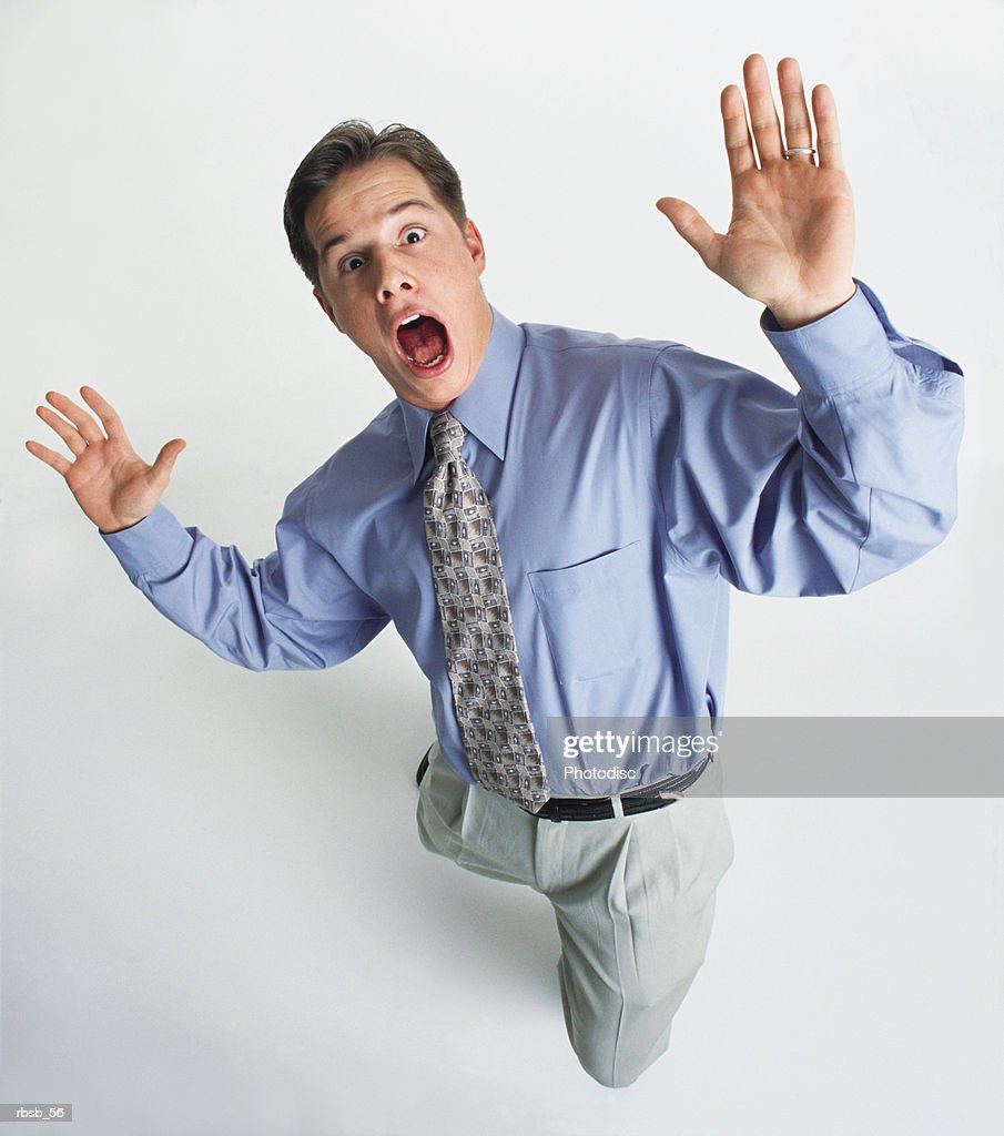 a handsome young caucasian man in a blue dress shirt and tan pants is looking up into the camera with a shocked expression on his face and his hands out in a suprised gesture : Foto de stock