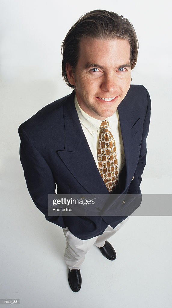a handsome young caucasian man with long dark hair dressed in a blue blazer and light tan pants is looking up into the camera with his hands in his pockets : Foto de stock