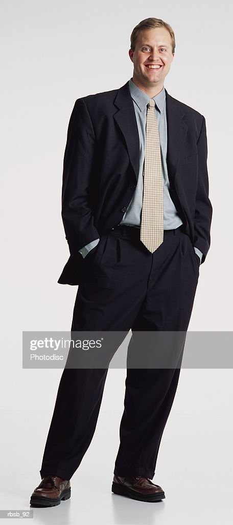 a handsome young caucasian man with short brown hair dressed in a dark business suit and green shirt standing looking into the camera with his hands in his pockets : Foto de stock