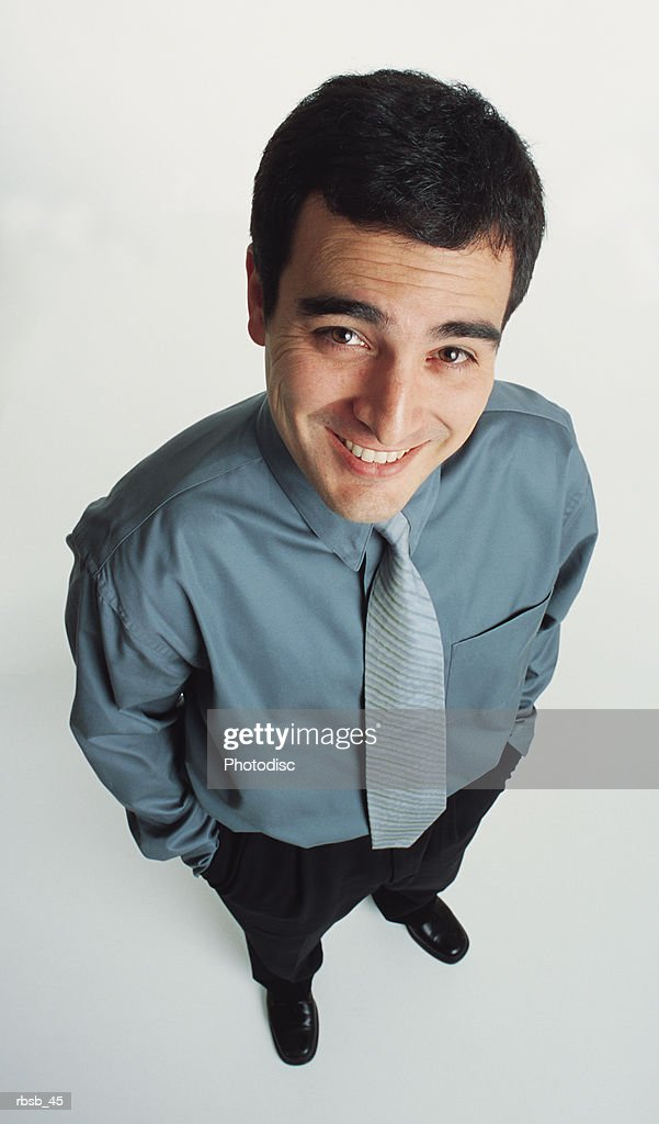 a handsome young caucasian man with short dark hair dressed in a blue shirt and dark slacks is looking up into the camera with a look of confidence : Foto de stock