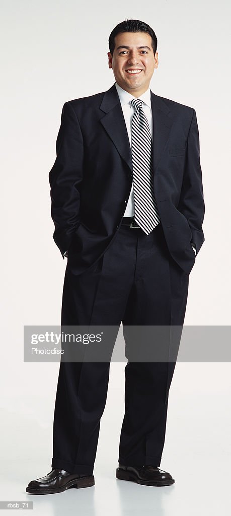 a handsome young ethnic businessman with short hair dressedin a dark suit and striped tie standing with his hands in his pockets looking into the camera : Foto de stock