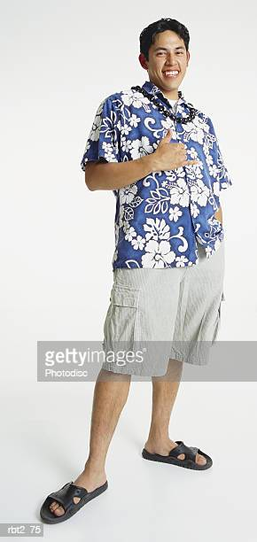 a handsome young latino man in a blue hawaiian shirt and shorts and sandals with a shell necklace gestures in sign language and smiles happily