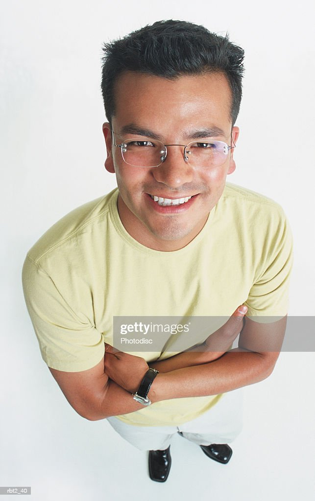 a handsome young latino man wearing glasses is looking up into the camera smiling and folding his arms across his chest : Foto de stock