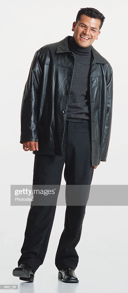 a handsome young latino man with glasses wearing black slacks and a black leather jacket stands casually smiling at the camera : Foto de stock
