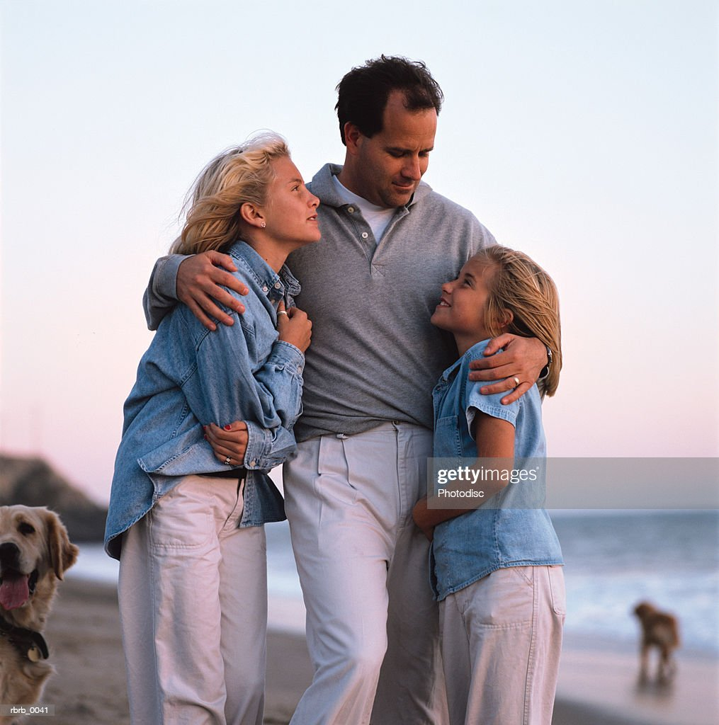 a happy caucasian family huddles together on the beach : Stockfoto