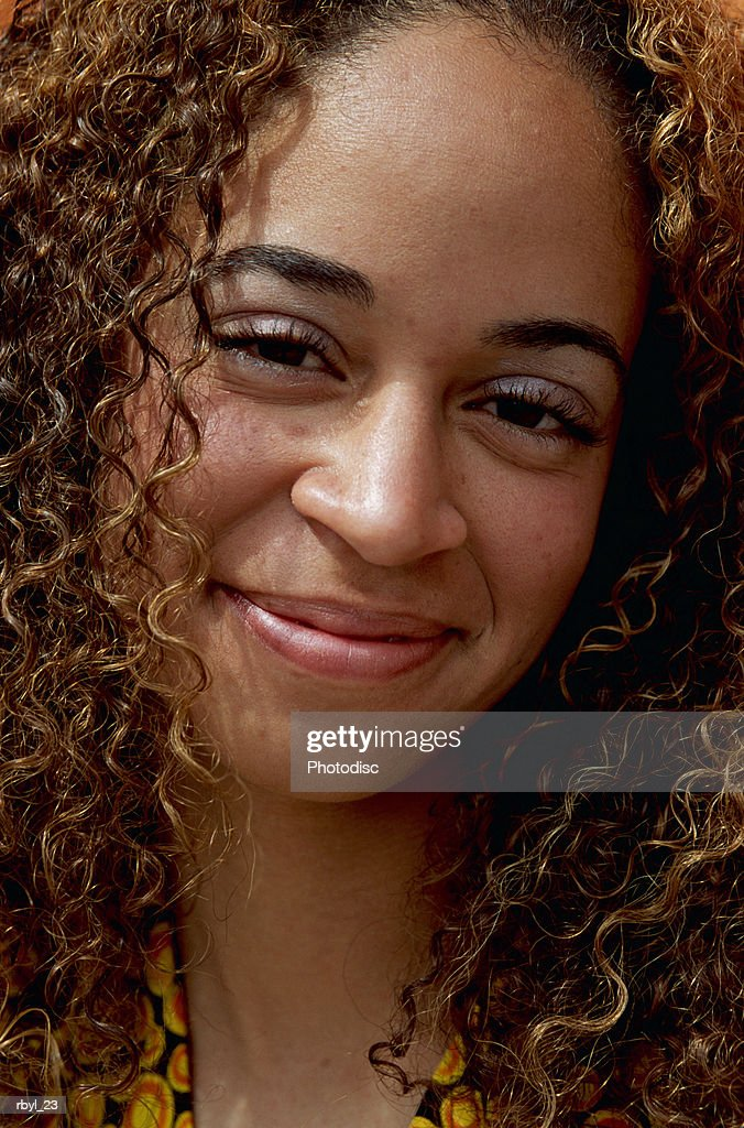 a head shot of a young african-american woman with long dark curly hair : Foto de stock