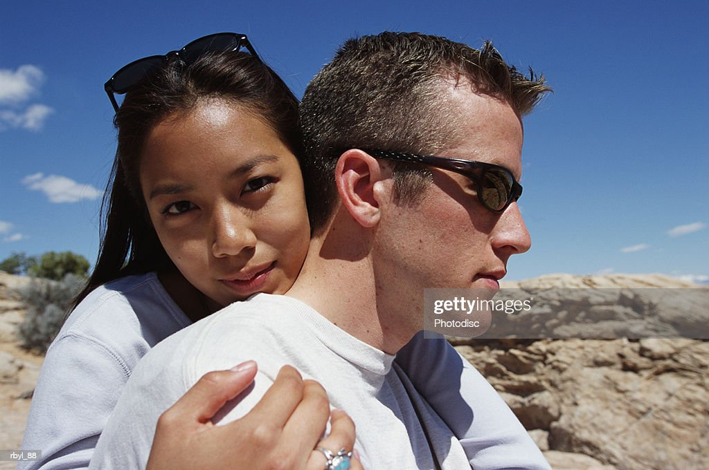 a head shot of a young couple standing in an embrace with the young lady looking at the camera and the young man standing profile to the camera with the south utah desert in the background : Stockfoto