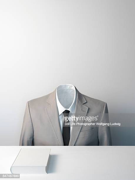 a headless body in a suit with white shirt and black tie sits in front of a white book on a plain white desk