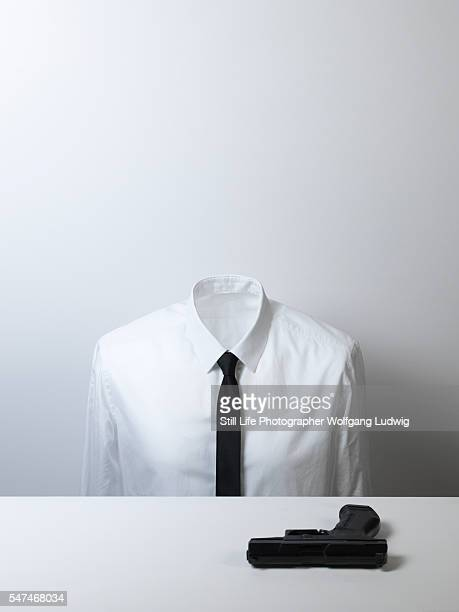 a headless body in a white shirt with a black tie sits in front of a black gun on a plain white desk