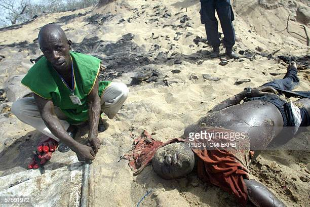 a Health worker tries to tie the stretcher beside a burnt body from oil blast at Ilado in Lagos 12 May 2006 Over 200 people were burnt beyond...