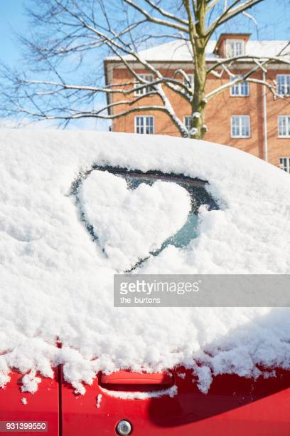 a heart drawn in snow on a car windshield