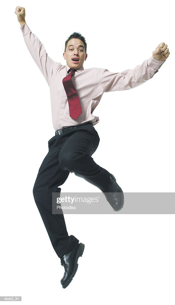 a hispanic business man in a pink shirt and tie jumps playfully up into the air : Foto de stock