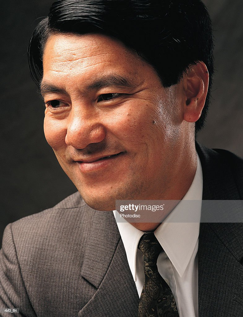 a hispanic businessman wearing a gray suit with shirt and tie smiles : Stockfoto