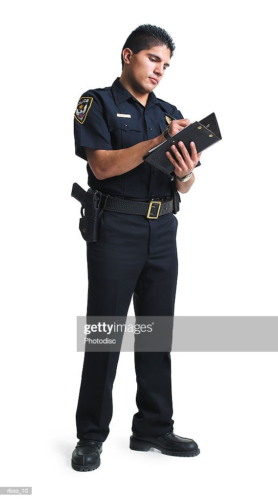 a hispanic male police officer stands as he writes a ticket : Stockfoto