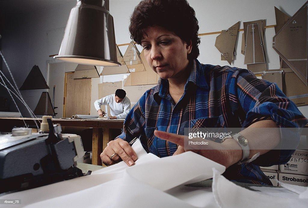 a hispanic woman cuts fabric in factory warehouse : Foto de stock