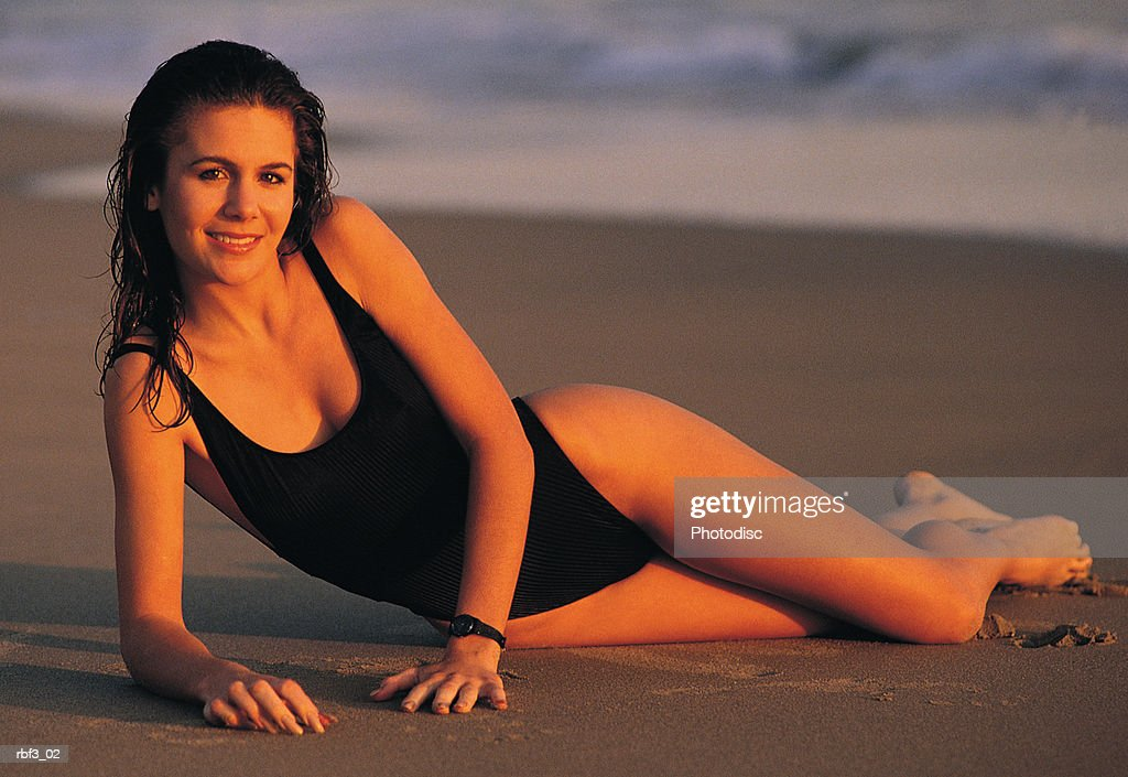 a hispanic woman wearing a black bathing suit lays on the wet sand of a beach as the waves roll behind her : Stockfoto