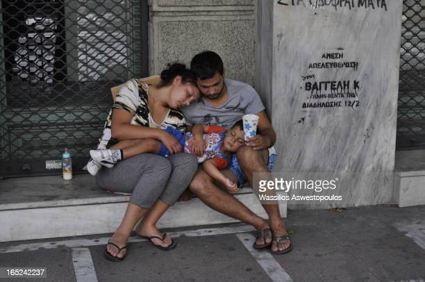 CONTENT] a homeless couple with their kid begging for help in the streets of athens
