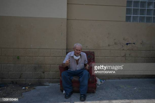 a homeless man with a protective mask around his neck sits on a couch in the streets of downtown San Salvador on March 30 2020 in San Salvador El...