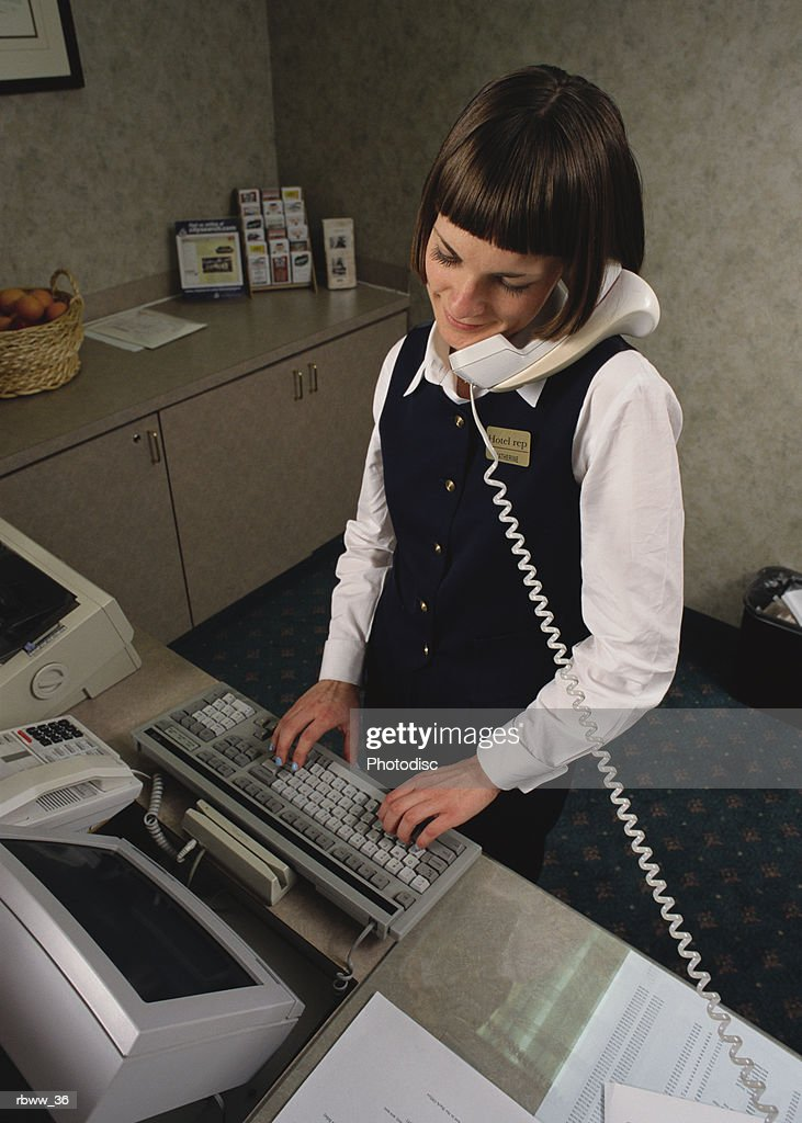 a hotel attendant logs a customer reservation onto a computer while speaking with him over the telephone : Foto de stock