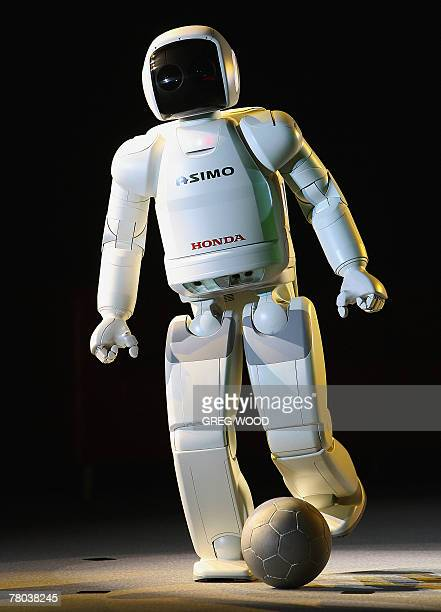 ASIMO a humanoid robot developed by Honda kicks a soccer ball on stage in Sydney 21 November 2007 as part of an extensive show tour around Australia...