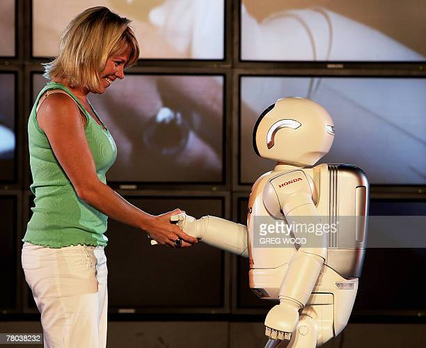 ASIMO a humanoid robot developed by Honda shakes hands with an unidentified woman on stage in Sydney 21 November 2007 as part of an extensive show...