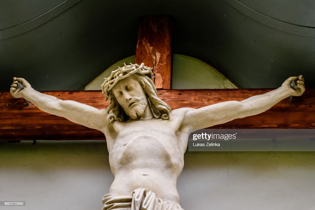 a Jesus statue on a cross carved from wood and painted : Stock Photo