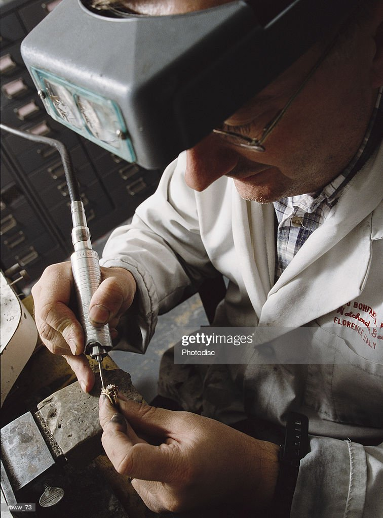 a jeweler repairs a diamond ring : Stock Photo