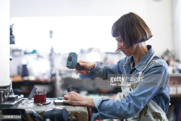a jewellery designer working in her studio. - craft product stock pictures, royalty-free photos & images