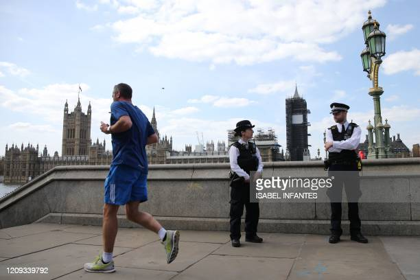 a jogger passes police officers outside St Thomas' Hospital in central London on April 7 2020 where Britain's Prime Minister Boris Johnson is in...