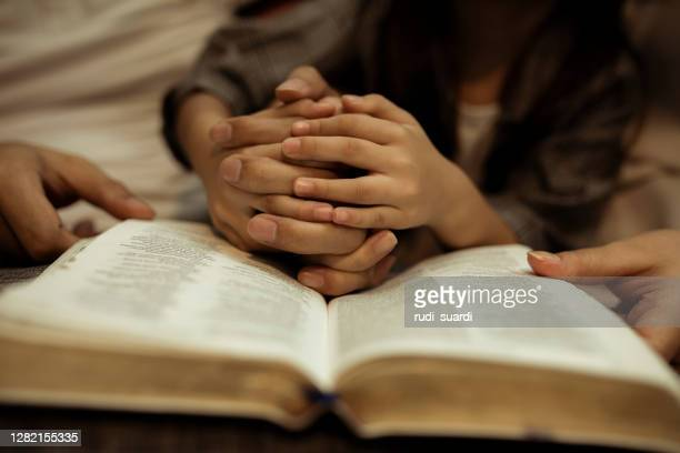 a kid reading the holy bible - prayer book stock pictures, royalty-free photos & images