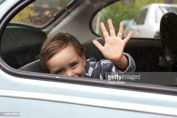 a kid touches the window of an old car from inside