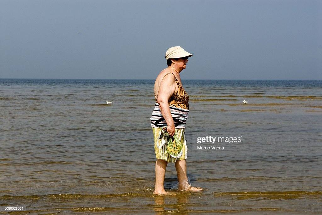 a lady, head covered with a hat, walks along the shore in Klaipeda on the Baltic Sea, Lithuania