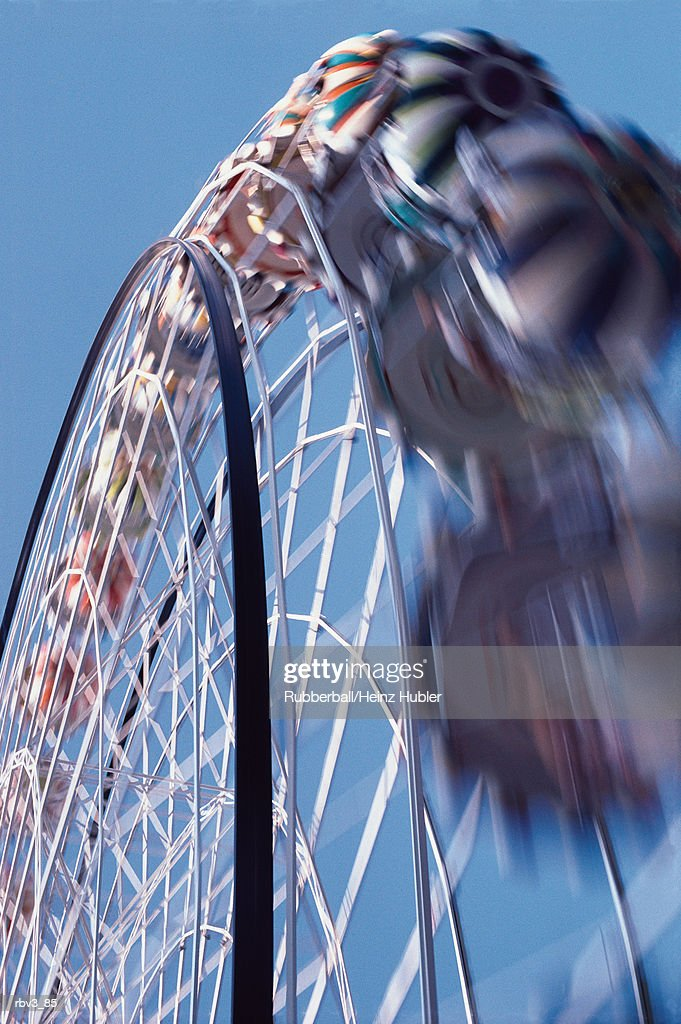 a large blurred white ferris wheel in motion below a blue sky : Foto de stock