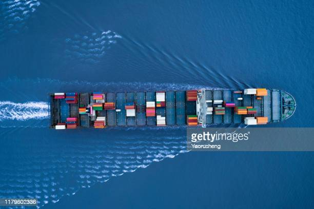 a large container ship is approching the port full loaded with containers and cargo - aerial - top down view - docks stock pictures, royalty-free photos & images