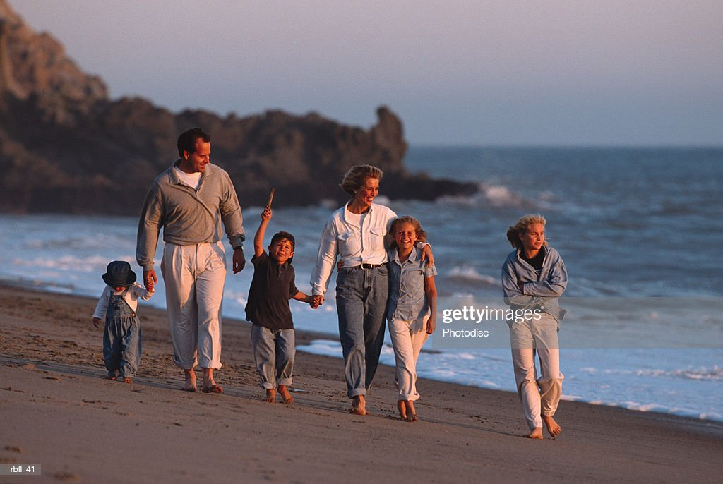 a large family walks along the beach at sunset : Stockfoto