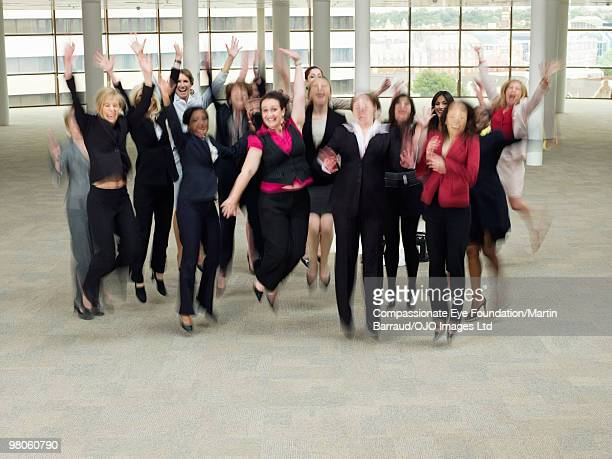 a large group of business women jumping in the air - compassionate eye foundation stock pictures, royalty-free photos & images