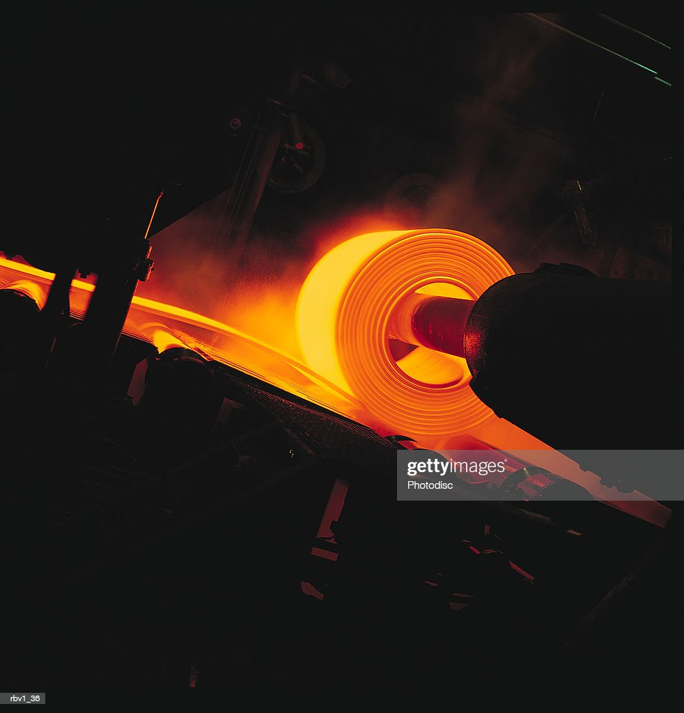 a large hot orange steel sheet is being rolled by a machine in a steel mill : Foto de stock