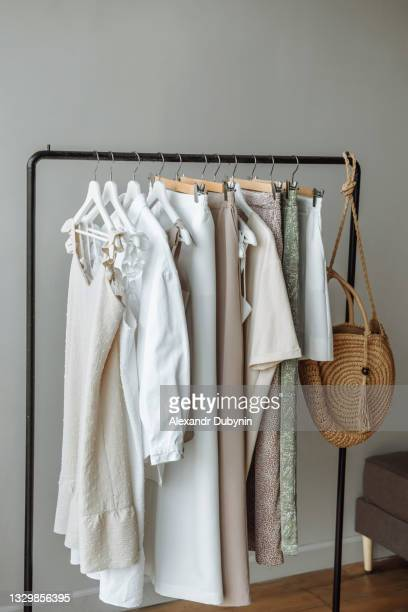 a large number of various clothes hanging on a rail in a store or at home - dress stock pictures, royalty-free photos & images